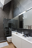 Graphic pattern on wall in modern bathroom in shades of grey