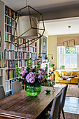 A wooden table with a bouquet of flowers in front of a floor-to-ceiling bookshelf