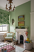 A bamboo chair and a toy basket by a fireplace in a children's room with a green wall