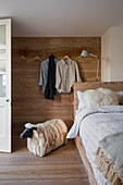 Bed in guest room with wood-clad wall