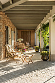 A sunny natural stone veranda with seating furniture