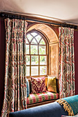 An arched window with a window seat and 1930s Art Deco-style curtains