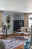 A bedroom corner with a black dresser, a decorative mirror and a 1930s Art Deco-style chinoiserie wallpaper