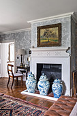 Urns in front of a fireplace in a bedroom with 1930s Art Deco-stlye chinoiserie wallpaper