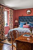 A bedroom with a double bed, a curtain and a 1930s Art Deco-style inlaid desk