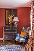 An upholstered armchair, a chest of drawers and 1930s Art Deco-style artwork