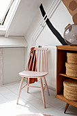 Pink spoke-back chair next to knee wall with fitted cupboards