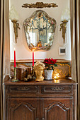 Bust, candle and poinsettia on old cabinet