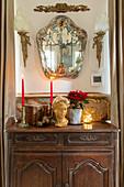 Büste, Kerzen und Weihnachtsstern auf einem alten Schränkchen