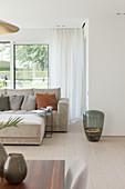 Bodenvase neben dem modernen Sofa im Wohnzimmer in Hellgrau