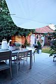 Tisch und Stühle auf der Terrasse im Hinterhofgarten bei Abendstimmung