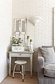 A shabby chic-style drawer table and a stool against a white-painted brick wall