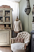 A comfortable upholstered armchair, a tailor's dummy and a shabby chic-style dresser