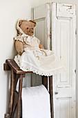 Verkleideter, alter Teddybär neben weißem Schrank in Shabby-Style