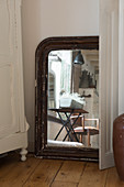 An old mirror on the wooden floorboards