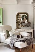 Helles Tagesbett mit Tierfell, Schubladenschrank und Wandspiegel im Wohnzimmer