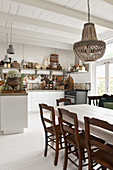 A dining table with chairs in an open-plan, shabby-chic style kitchen