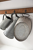 Old zinc containers on hooks