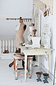 A statue and plants on a white, shabby-chic style table in front of a dressmaker's dummy