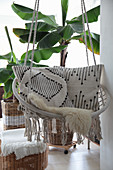 Scatter cushions with ethnic patterns in hanging chair in front of banana trees planted in baskets