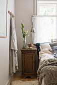 A bedside table next to a bed in a rural bedroom