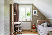 A bed and a desk in a girl's room with wallpaper in the attic