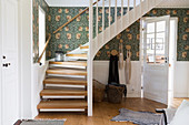 An entrance hall with wooden stairs, white cassette cladding and wallpaper