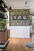A view of children's photos on a wallpapered wall