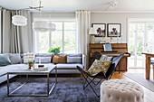 Blau-graues Polstersofa, Klassikersessel und Klavier im Wohnzimmer