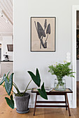 A house plant next to a small table with a flower and a picture hanging above it