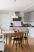 A wooden table with chairs in a bright kitchen with a wooden ceiling