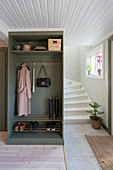 An open wardrobe with a shoe rack in a hallway
