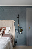 Double bed with bed linen and bedspread in beige, in front of a gray wall