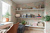 Shelves, an upholstered stool and a desk with a leather chair in a room with floral wallpaper