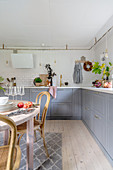 Round wooden dining table and base cabinets with gray fronts in the kitchen