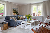 A coffee table and a blue upholstered sofa in a living room with patterned wallpaper