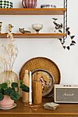 Vase, Holzflasche, Tablett und Vintage Radio, darüber Regal mit Dekoobjekten