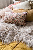 Cushions and fur blanket on double bed