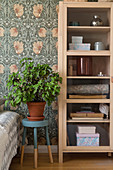 Houseplant on stool between bed and cupboard with glass door