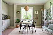 Round table and chairs in kitchen-dining room with patterned wallpaper