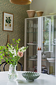 View past flowers on table to glass-fronted cabinet