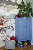 A houseplant on a blue cupboard in a children's room in front of a wall papered with wallpaper with a landscape picture