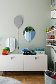 A lowboard in a children's room with a balloon lamp above it and a mirror on the wall