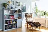 A cosy chair with a footstool next to a bookshelf in front of the window in a living room