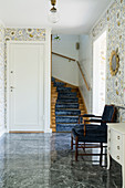 A cosy chair in front of a staircase in a hallway with floral wallpaper