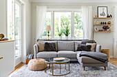 Graues Polstersofa auf farblich passendem Teppich in hellem Wohnzimmer
