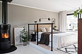 A double bed in a sleeping area with an iron railing as a room divider and fireplace