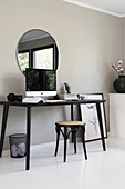 A home office on a kitchen table in front of a grey wall