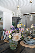 Flowers on a laid wooden table with lights with glass shades hanging above it