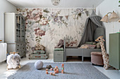 A bed with a curtain in front of a wall papered with floral wallpaper in a matt-coloured girl's room